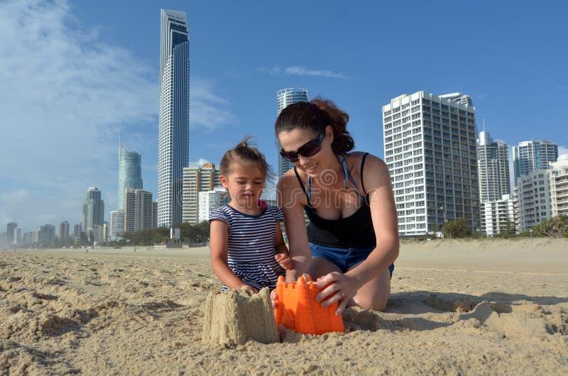 De moeder en de dochter bouwen zandkasteel in Surfersparadijs Austr royalty-vrije stock fotografie