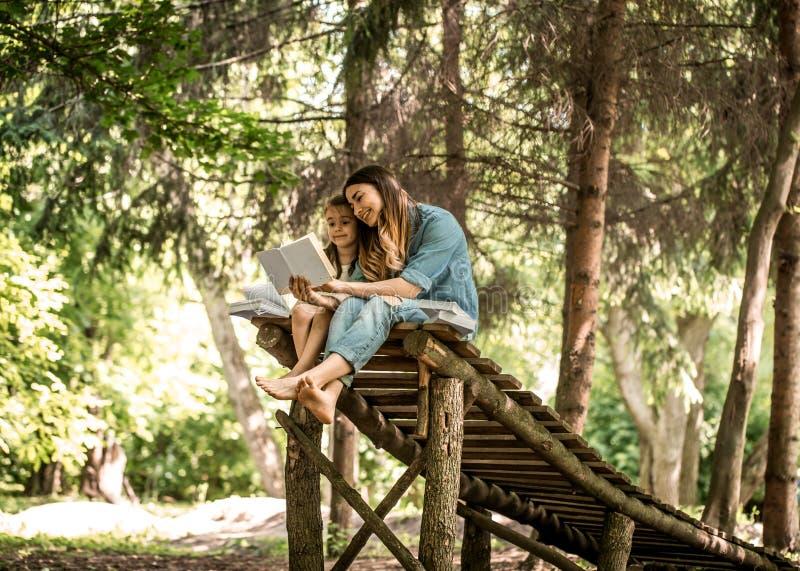 De moeder en de dochter lezen een boek in het park royalty-vrije stock fotografie