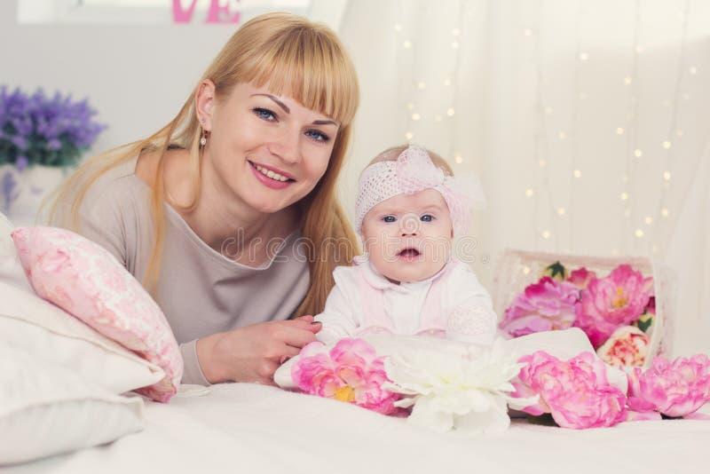 De moeder en de dochter liggen op bed met roze bloemen royalty-vrije stock fotografie