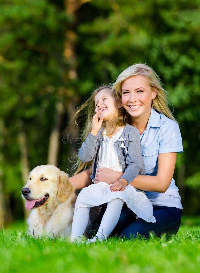 De moeder en de dochter met golden retriever zijn op het gras stock foto