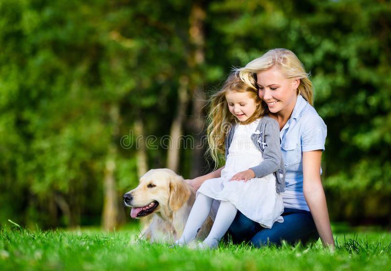 De moeder en de dochter met Labrador zijn op het gras stock afbeelding