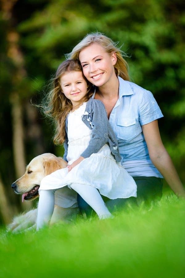 De moeder en de dochter met Labrador zitten op het gras stock afbeeldingen