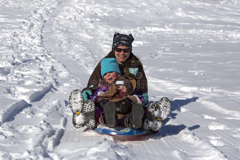 De moeder en de kinderen hebben pret glijdend onderaan de sleeheuvel stock fotografie