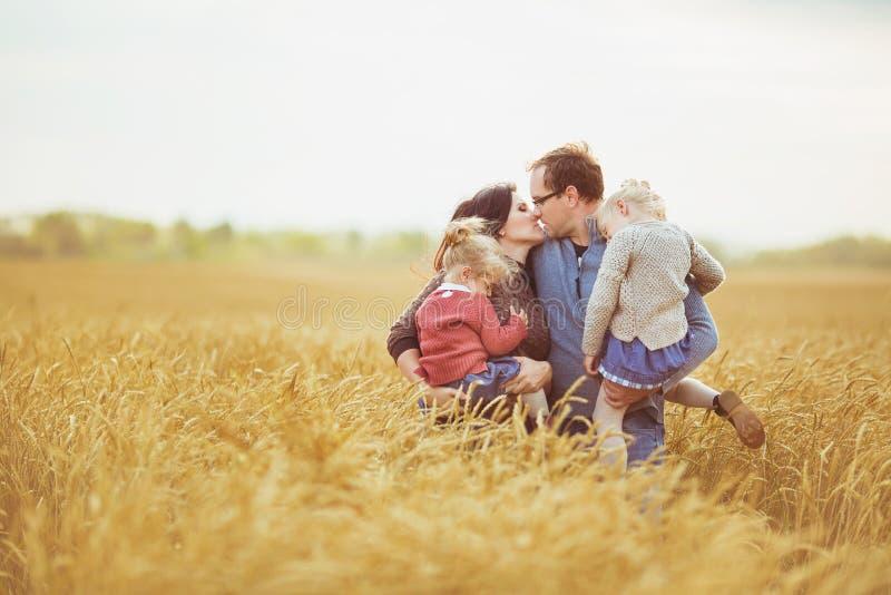 De moeder en de vader houden op handen hun kleine kinderen en kus elkaar op een gebied stock foto