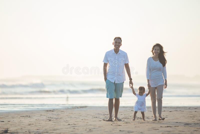 De moeder en de vader onderwijzen haar dochtergangen op het strand royalty-vrije stock foto's