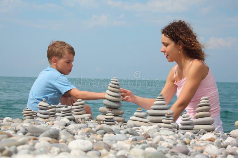 De moeder en de zoon bouwen steenstapels op strand royalty-vrije stock foto