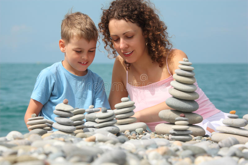 De moeder en de zoon bouwen steenstapels op strand royalty-vrije stock foto's