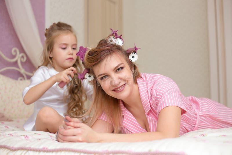 De moeder en de dochter doen haar en hebben pret stock foto's