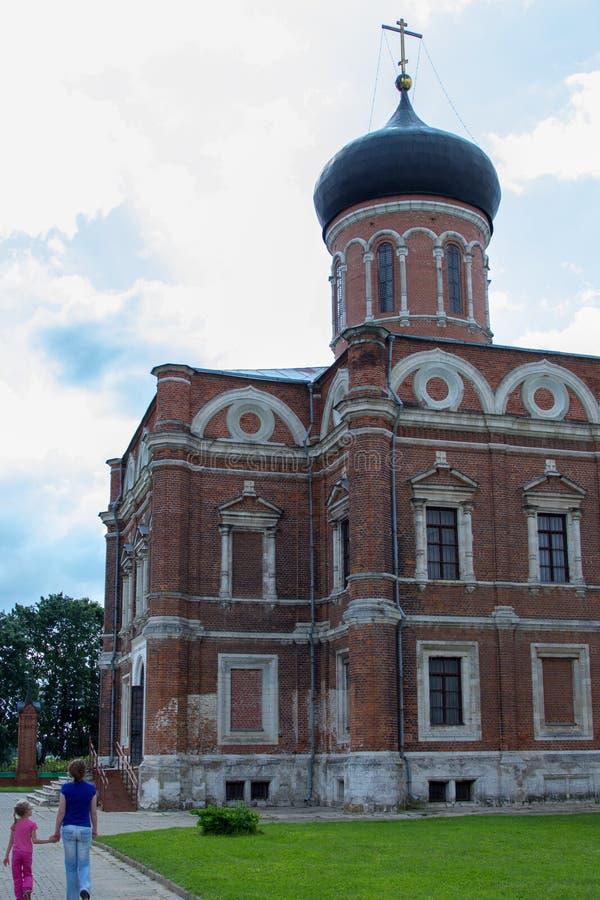 De moeder en de dochter gaan naar oude orthodoxe kerk stock foto