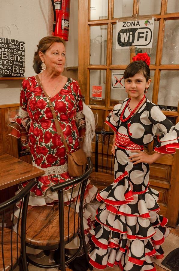 De moeder en de dochter of de kleindochter en de grootmoeder kleedden zich in sevillanas bij de deur van een bar in Granada bij d royalty-vrije stock foto
