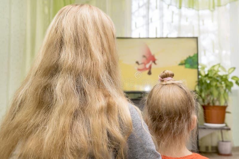 De moeder en de dochter letten op TV stock afbeelding