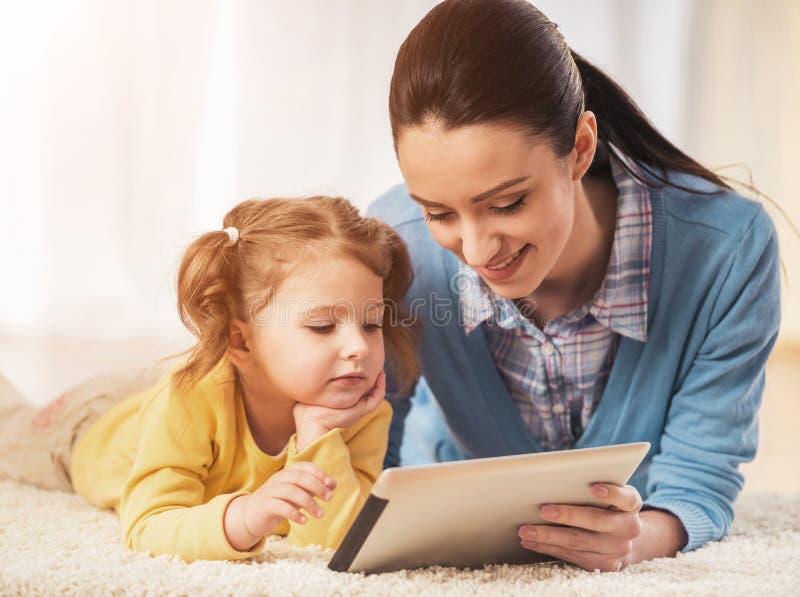 De moeder en de Dochter liggen op Tapijt met Tablet stock foto