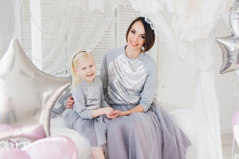 De moeder en de dochter in mooie uitrustingen vieren de vakantie royalty-vrije stock afbeeldingen