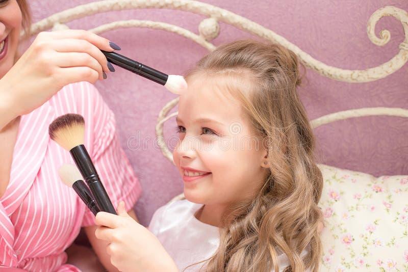 De moeder en de dochter passen samen make-up toe stock fotografie