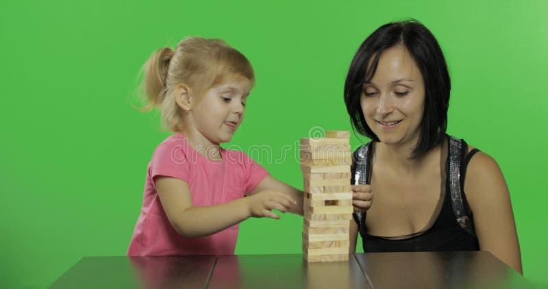 De moeder en de dochter spelen jenga Het kind trekt houten blokken van toren stock fotografie