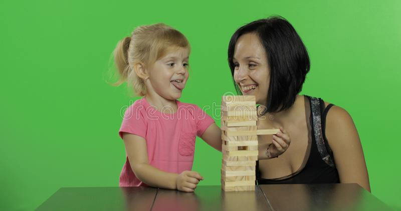 De moeder en de dochter spelen jenga Het kind trekt houten blokken van toren royalty-vrije stock foto's