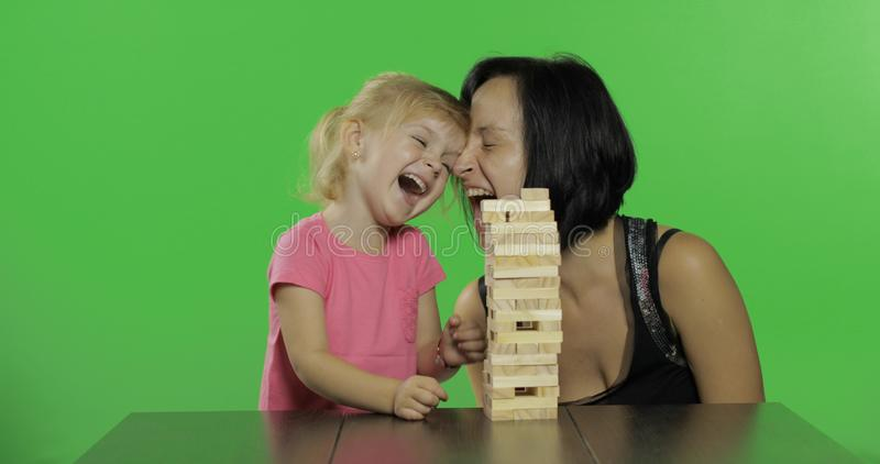 De moeder en de dochter spelen jenga Het kind trekt houten blokken van toren stock foto's