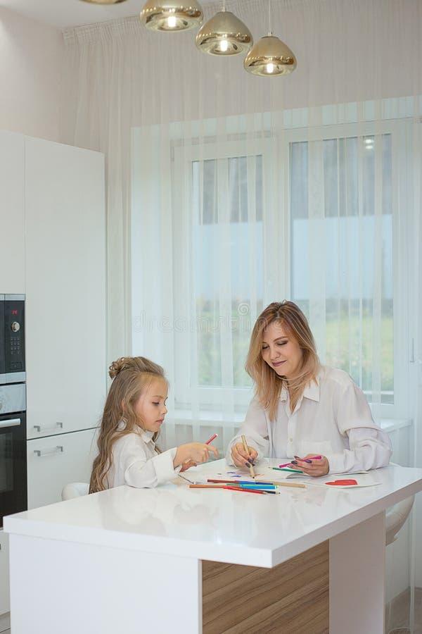 De moeder en de dochter trekken zich thuis samen stock afbeeldingen