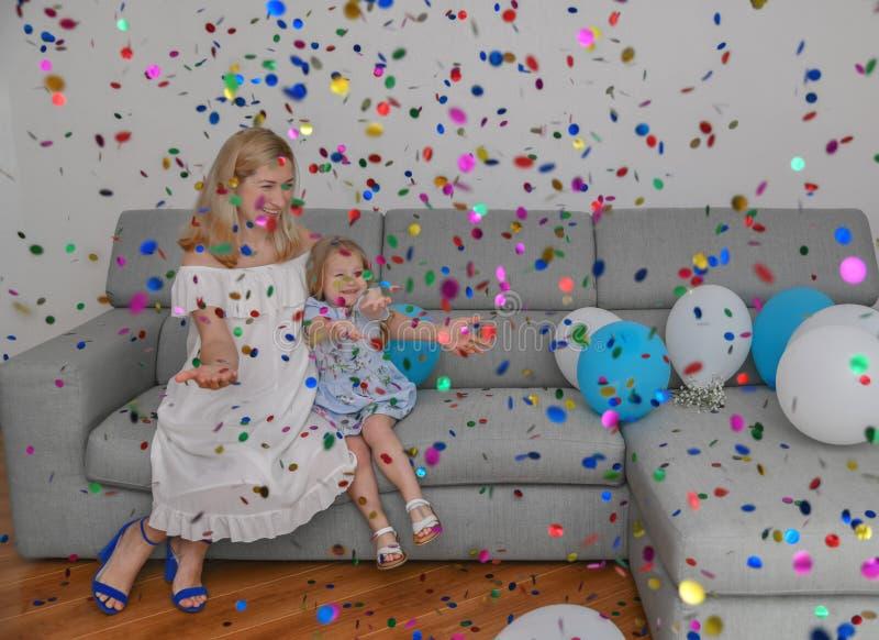 De moeder en de dochter vieren verjaardag met impulsen en confettien royalty-vrije stock foto