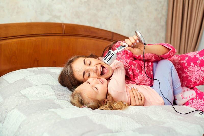 De moeder en de dochter zingen samen de liederen van de pretkaraoke in de ruimte stock foto