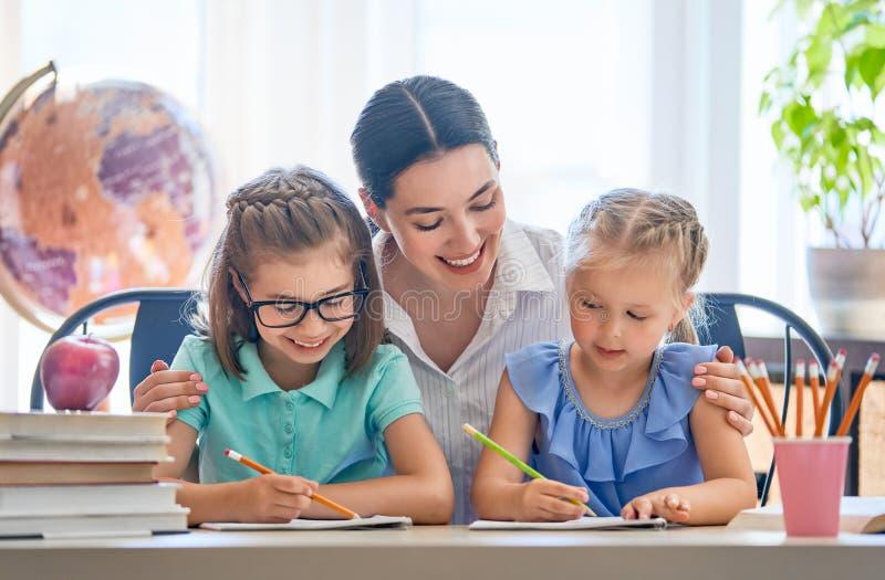 De moeder en de dochters leren te schrijven royalty-vrije stock afbeelding