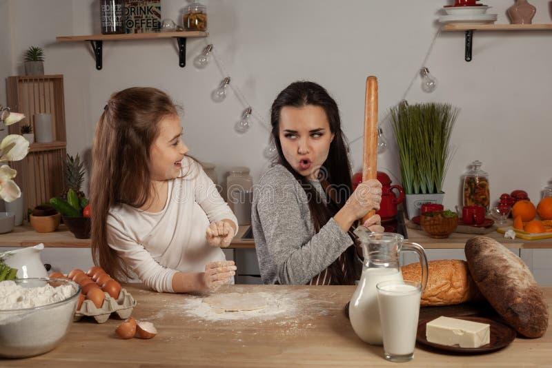 De moeder en haar dochter bakken een brood en hebben pret bij de keuken stock fotografie