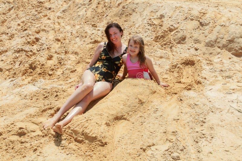 de moeder en haar dochter maken tot een kleine omhelzing het zand van het strand stock afbeelding
