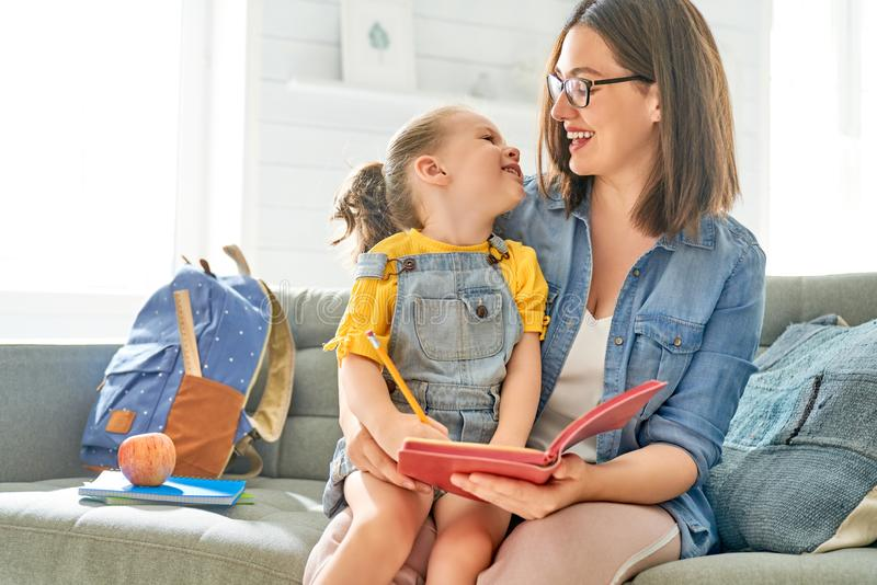 De moeder en haar dochter schrijven in notitieboekje stock foto