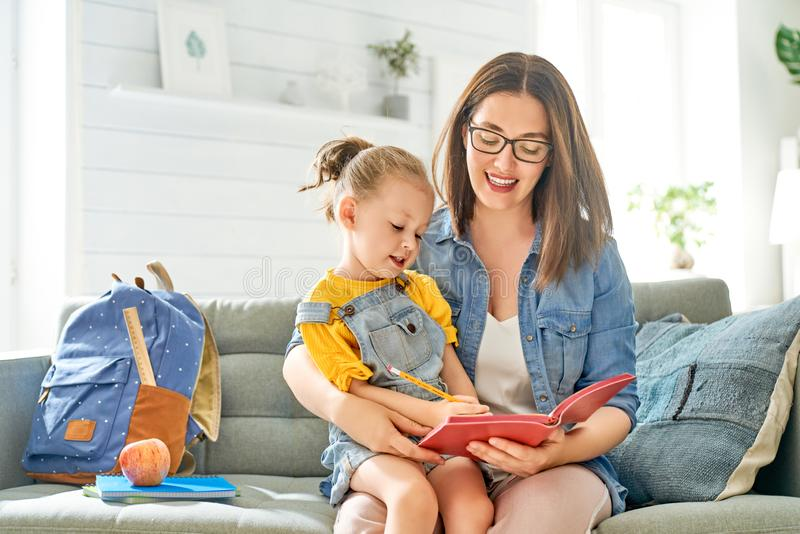 De moeder en haar dochter schrijven in notitieboekje stock afbeelding