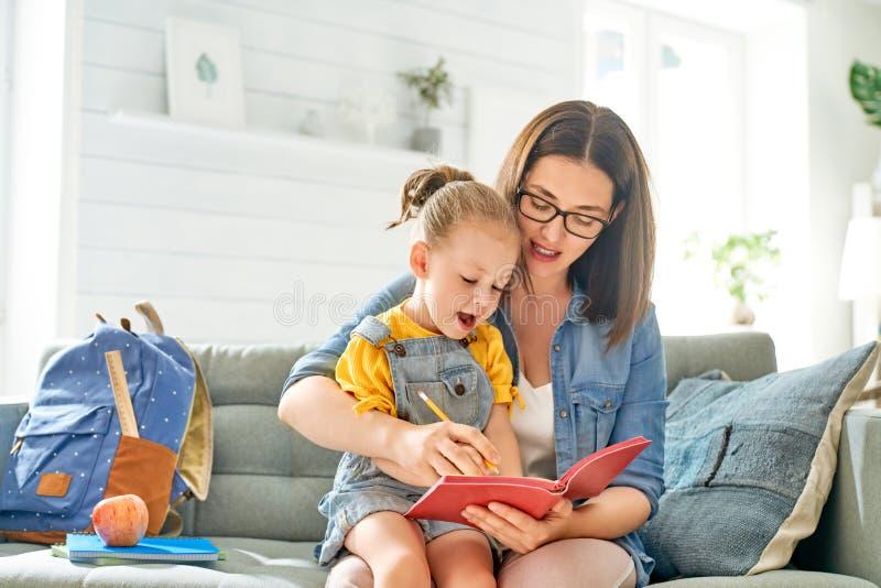 De moeder en haar dochter schrijven in notitieboekje royalty-vrije stock foto