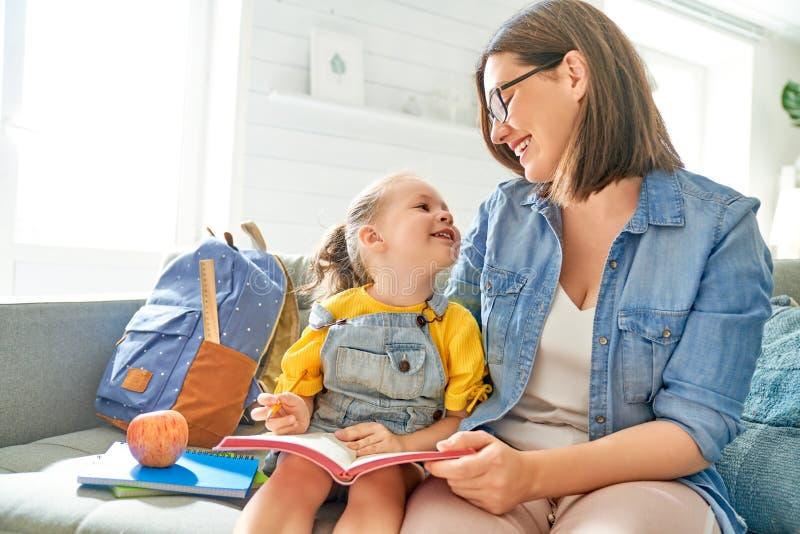De moeder en haar dochter schrijven in notitieboekje stock foto's