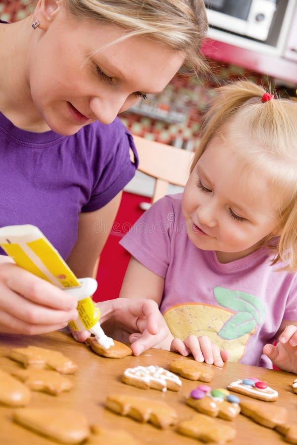 De moeder en haar dochter verfraaien gemberbrood stock afbeeldingen