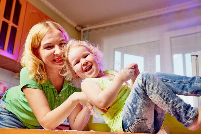De moeder en haar drie jaar oude blondedochter koken in een keuken Gelukkig mamma en klein meisje stock fotografie