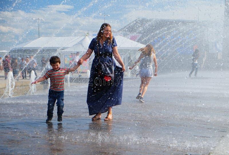 De moeder en haar kind lopen onder de stralen van de fontein tijdens de hittegolf royalty-vrije stock fotografie