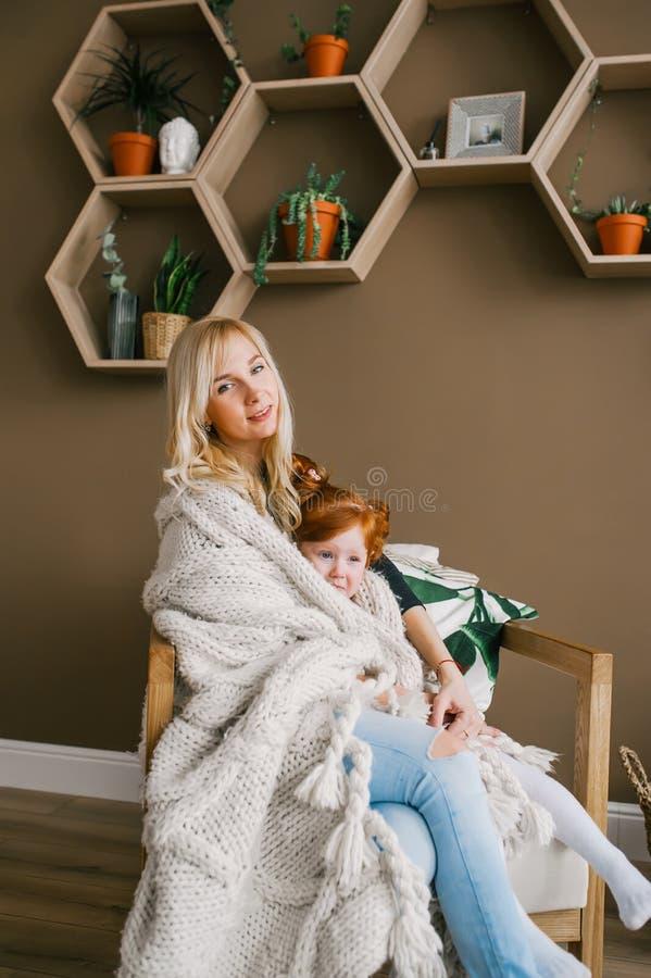 De moeder en haar mooie roodharigedochter zitten thuis in de leunstoel, omhelzingen, die pret hebben stock foto