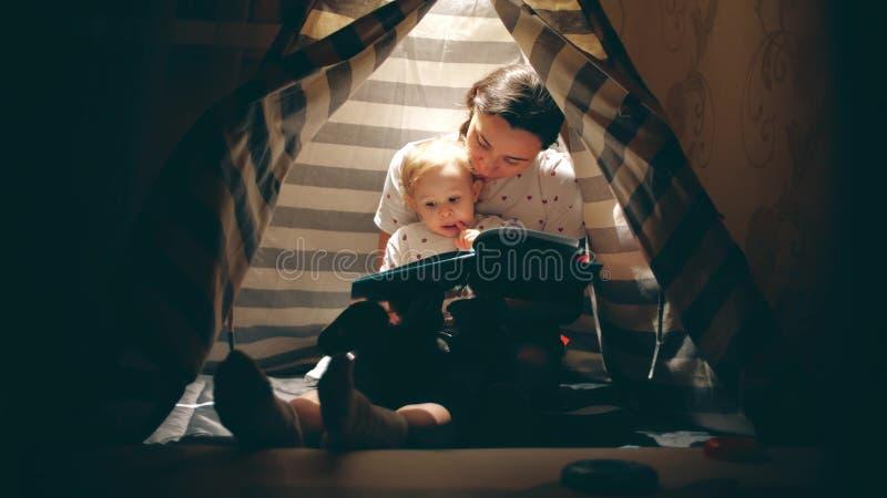 De moeder en haar weinig baby lezen samen een boek in een comfortabel aangestoken tipi in de avond stock afbeeldingen