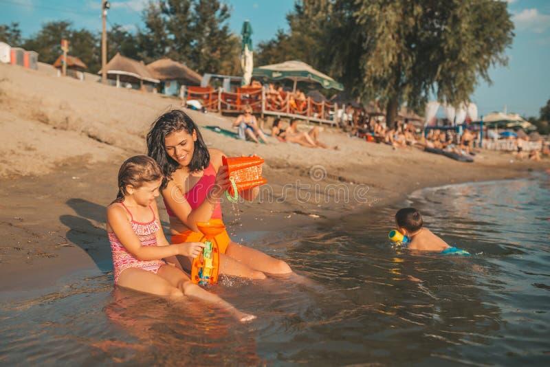 De moeder en haar weinig gelukkige dochter spelen met strandspeelgoed in het water royalty-vrije stock afbeeldingen