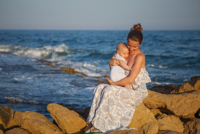 De moeder en haar zoon hebben pret bij het overzeese strand bij de zonsondergang stock afbeeldingen
