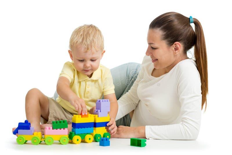 De moeder en het kind bouwen uit kleurrijke plastic blokken Familie en kinderjarenconcept stock foto's