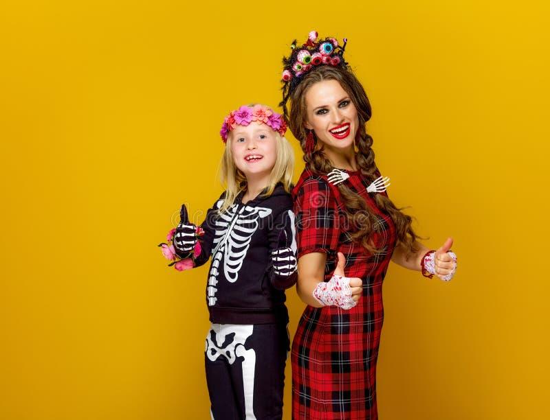 De moeder en het kind in Halloween-kostuum het tonen beduimelen omhoog stock afbeelding