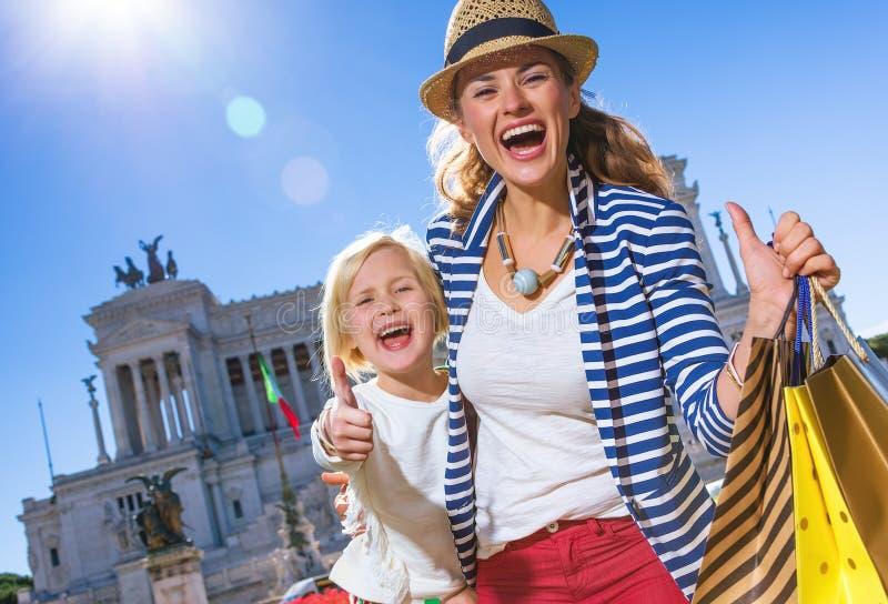 De moeder en het kind met het winkelen zakken het tonen beduimelen omhoog royalty-vrije stock foto