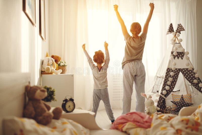 De moeder en het kind rekken zich na ontwaken in de ochtend uit royalty-vrije stock fotografie