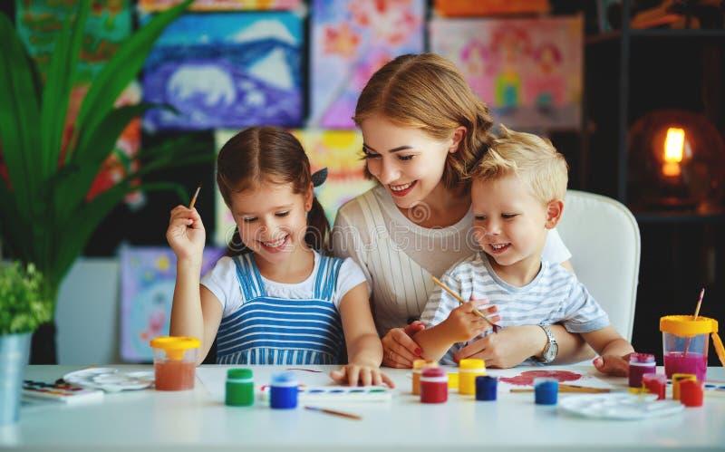 De moeder en het schilderen van de van de kinderenzoon en dochter trekken in creativiteit in kleuterschool stock afbeeldingen