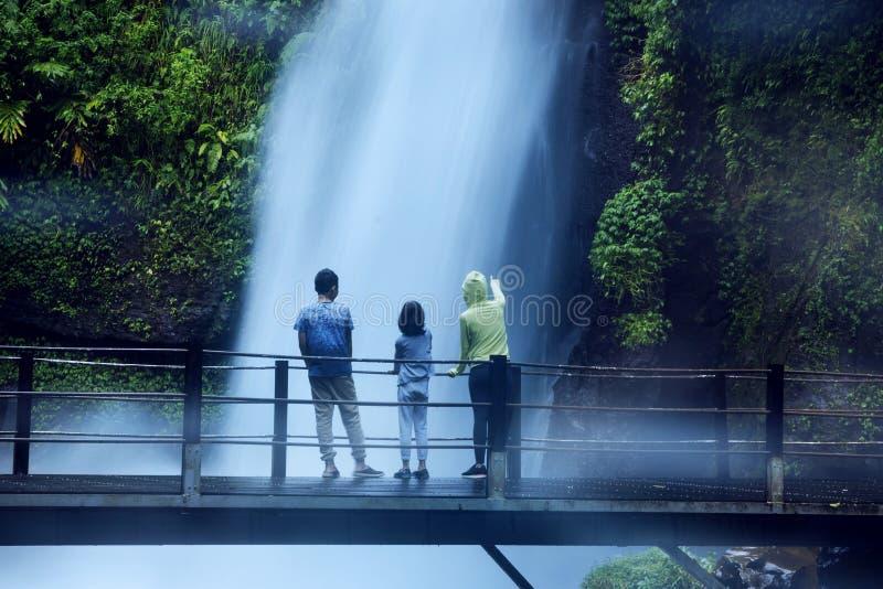 De moeder en de kinderen genieten de waterval van mening van Situ Gunung stock foto's