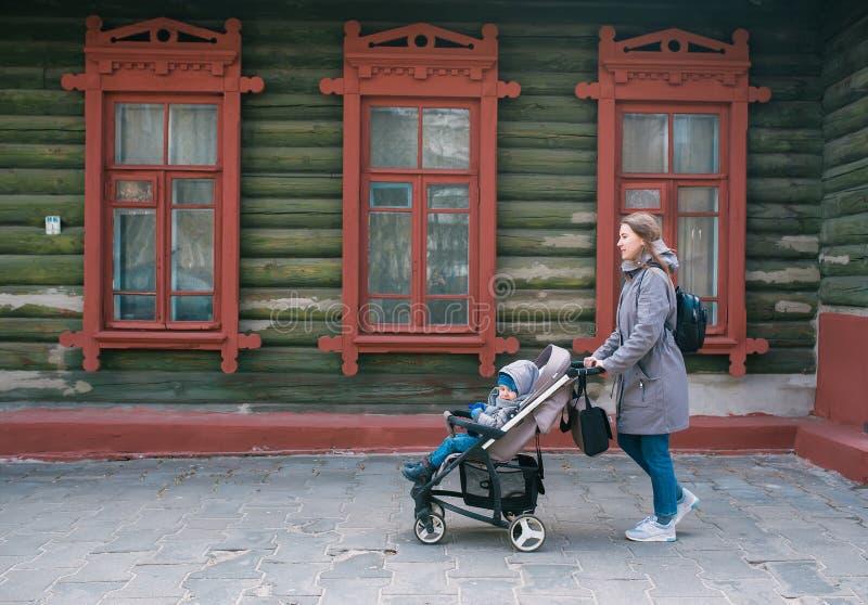 De moeder en de kleine zoon in een wandelwagen lopen op de stadsstraat langs het grote oude blokhuis stock afbeeldingen
