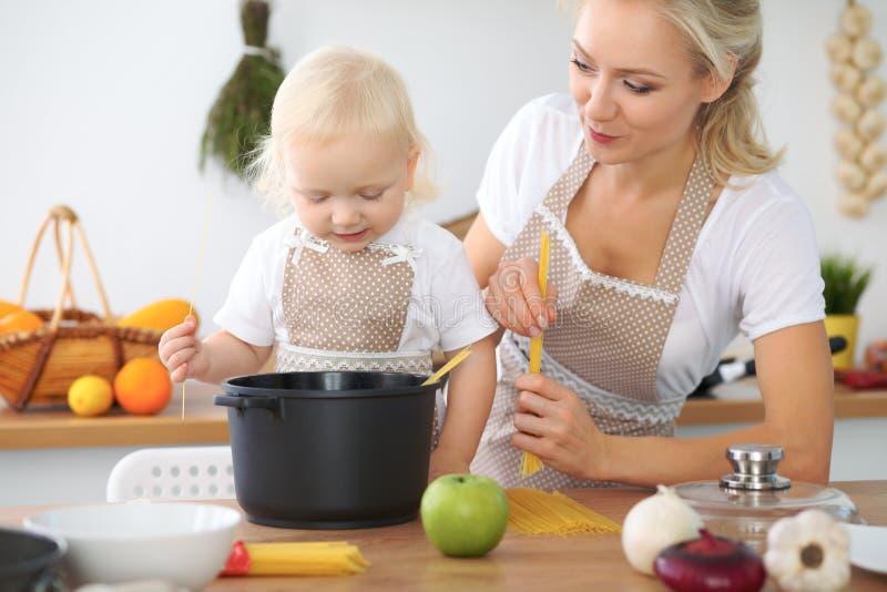 De moeder en weinig dochter koken in de keuken Het besteden samen alle tijd of gelukkig familieconcept royalty-vrije stock fotografie