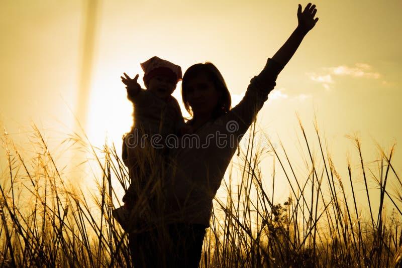 De moeder en weinig dochter silhouetteren bij zonsondergang stock foto