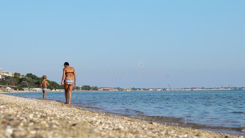 De moeder en weinig zoon nemen een gang op strandkust royalty-vrije stock foto's