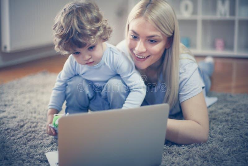 De moeder en de zoon hebben het spelen met laptop stock foto