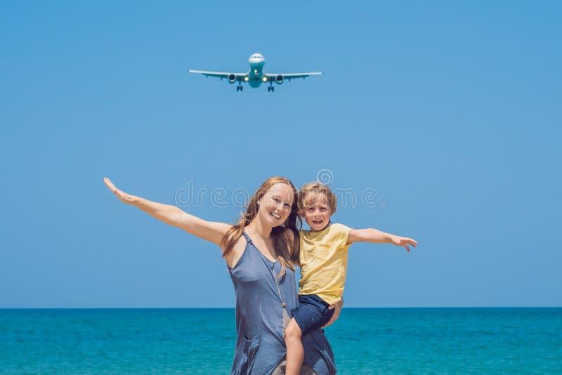 De moeder en de zoon hebben pret op het strand lettend op de landende vliegtuigen Het reizen op een vliegtuig met kinderenconcept royalty-vrije stock foto